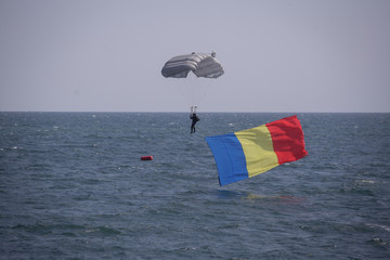 A Romanian navy paratrooper lands in water with the Romanian flag, during the Romanian Navy Day