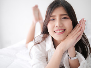 Happy Asian woman relaxing on bed, lifestyle concept.