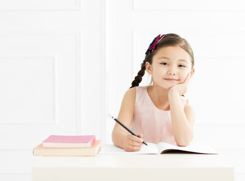 little girl with book studying at home