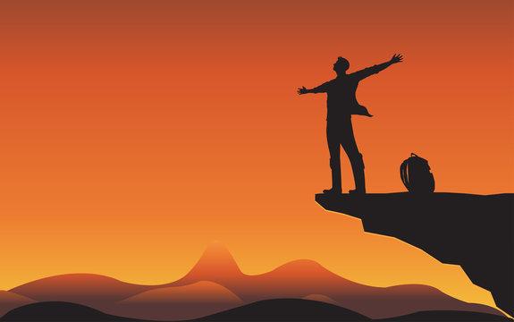 Sillhouette man on mountain cliff