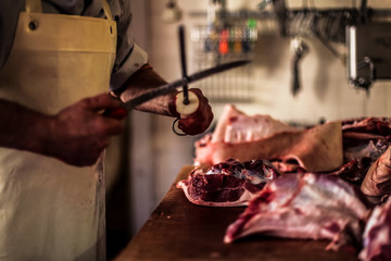 butcher cut raw meat with a knife at table in the slaughterhouse
