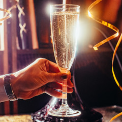 Party and holiday celebration concept. Glass with champagne in hand. Toned image.