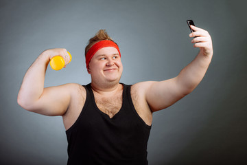 Funny smile fat man wearing black shirt with big belly, pumping biceps and doing selfie on grey background