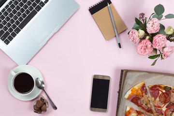 Top view of office gadgets, coffee, mobile phone and pizza on a pink background, flat lay