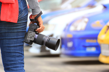 Photographer holding DSLR camera in his hands with standing at the car parking lot