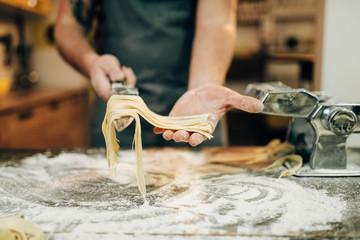 Chef cooking fettuccine in pasta machine