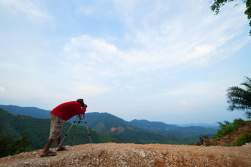 Professional photographer taking a picture of landscape beautiful mountain in rainforest.