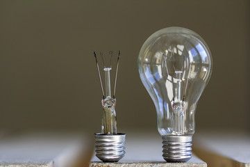 One broken and one whole electric light bulb on blurred background.