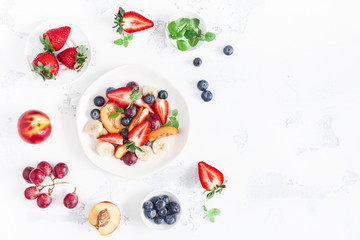 Fruit salad with strawberry, blueberry, peach, banana, grape and fresh fruits on white background. Flat lay, top view, copy space Fototapete