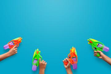Hands holding plastic water gun on blue background