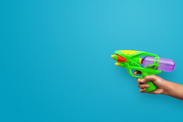 Hand holding plastic water gun on blue background. Objects with clipping path