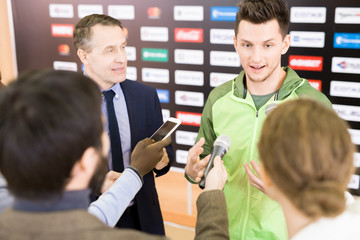 Group of highly professional reporters standing at talented young athlete and interviewing him after successful performance in competition