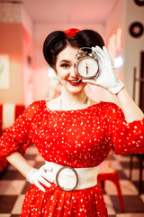 Smiling pin up girl posing with alarm clock,