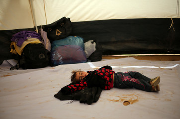 Palestinian girl sleeps inside a tent during a tent city protest along the Israel-Gaza border, demanding the right to return to their homeland, in the southern Gaza Strip