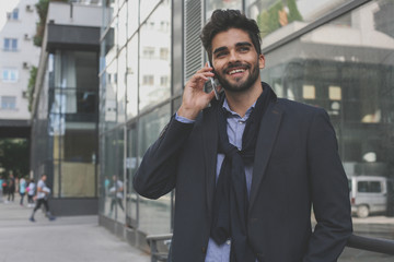 Young businessman using smart phone outdoor.