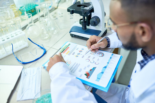 Close-up of busy concentrated Arabian male scientist viewing charts while holding medical research and sitting at table with glassware and equipment in modern laboratory