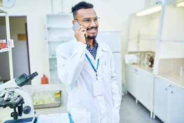 Cheerful excited handsome Arabian laboratory employee with hanging badge on neck communication with colleague on mobile phone and laughing