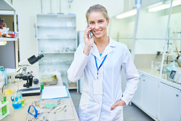 Cheerful optimistic experienced attractive female chemist with badge looking at camera while calling on mobile phone in laboratory