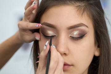 Beautiful young woman getting eyeliner done at a beauty salon