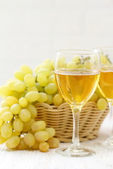 Glass of wine and grapes in the basket on a wooden table.