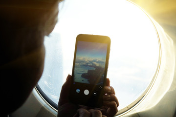 Woman taking pictures from the window of the plane.