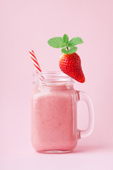 Strawberry smoothie or milkshake in mason jar decorated mint on pink pastel table. Healthy food for breakfast and snack.
