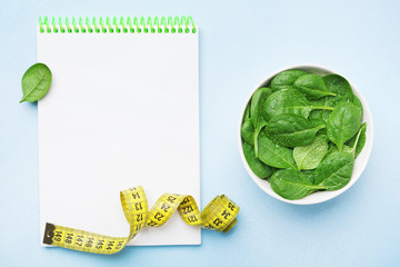 Empty notebook, green spinach leaves and tape measure on blue table top view. Diet and healthy food concept.