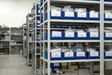Fototapeta Plastic trays and cardboard boxes in metal racks. obraz