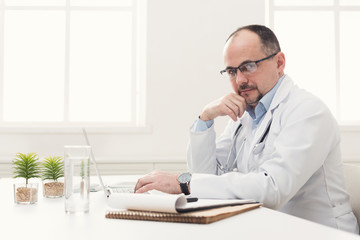 Serious doctor in glasses typing on laptop