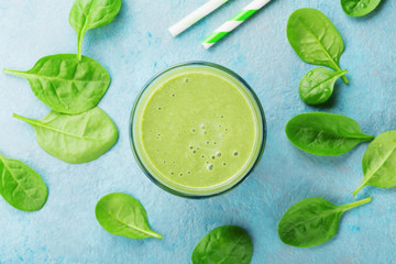 Green spinach smoothie on blue table top view. Detox and diet food for breakfast.
