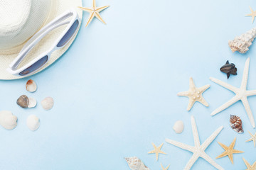 Summer holidays background from seashells and starfish with hat and sunglasses top view. Travel and trip concept.