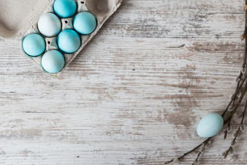 Easter background with eggs on a white wooden table. View from above