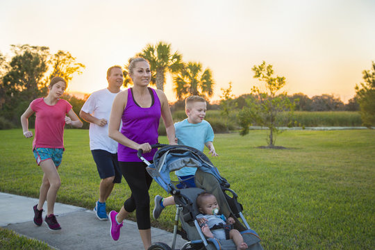 Beautiful, fit young family walking and jogging together outdoors along a paved sidewalk in a park pushing a stroller at sunset