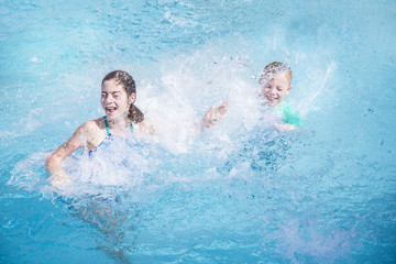 Two cute kids laughing and splashing each other in the swimming pool while on a summer vacation . Water is splashing everywhere and kids are having lots of fun