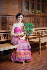 pretty woman with thai dress hold peacock fan in thai wooden old style house