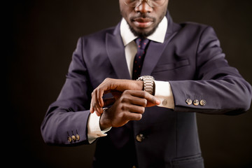 close up cropped image african male of setting of watch.live according to timetable. synchronize watches