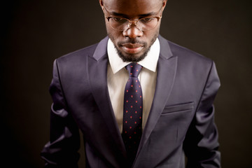 top view shot of good-looking black model wearing glasses in classical outfit isolated on the black background.guilty look
