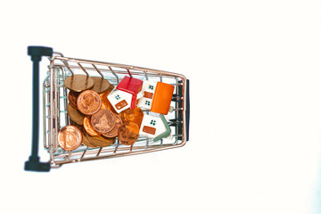 Closeup miniature house with golden stack coins in mini shopping cart isolated on white background using as business, property and financial concept - Vintage filter
