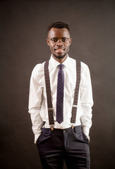 Portrait of happy young trendy African man with glasses, suspenders, white shirt, trousers and tie on black background.