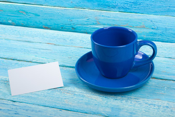 Blank business cards, blue cup on the wooden table. Template for ID. Top view. A cup of coffee.