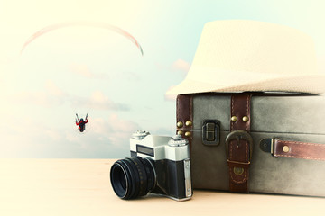 traveler vintage luggage, camera and fedora hat over wooden table infront of blue sky and parachute sport. holiday and vacation concept.