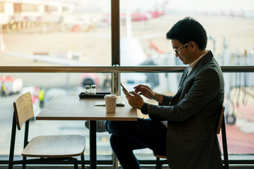 Young asian businessman with suits sitting while using smartphone with happiness and a cup of hot coffee and passport put on a table at waiting area in international airport with airplane on runway