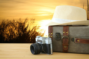 traveler vintage luggage, camera and fedora hat over wooden table infront of a field at sunset light. holiday and vacation concept.