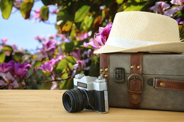 traveler vintage luggage, camera and fedora hat over wooden table infront of . holiday and vacation concept.