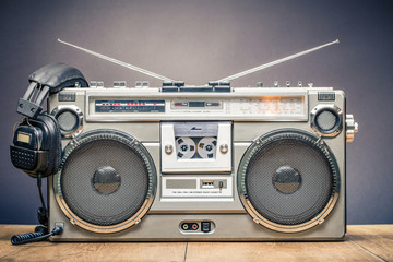 Retro outdated portable stereo boombox radio cassette recorder from circa late 70s with aged headphones front gradient black wall background. Listening music concept. Vintage old style filtered photo