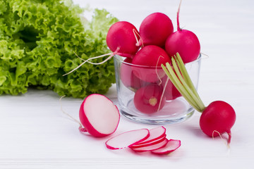 Radishes and lettuce on white background. Whole and sliced radishes close up. Fresh green lettuce. Eat better and feel better.