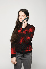 Young brunette teen girl talking on the phone, isolated on a white background