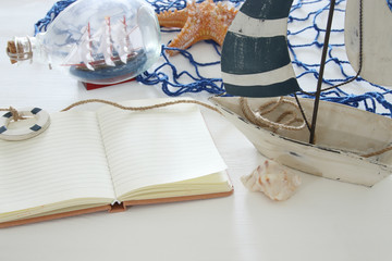 nautical concept image with white decorative sail boat and empty open notebook over white wooden table