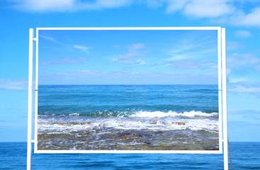 Image of white billboard on the beach with sea photo.