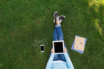 Top view of woman sitting on the green grass with tablet